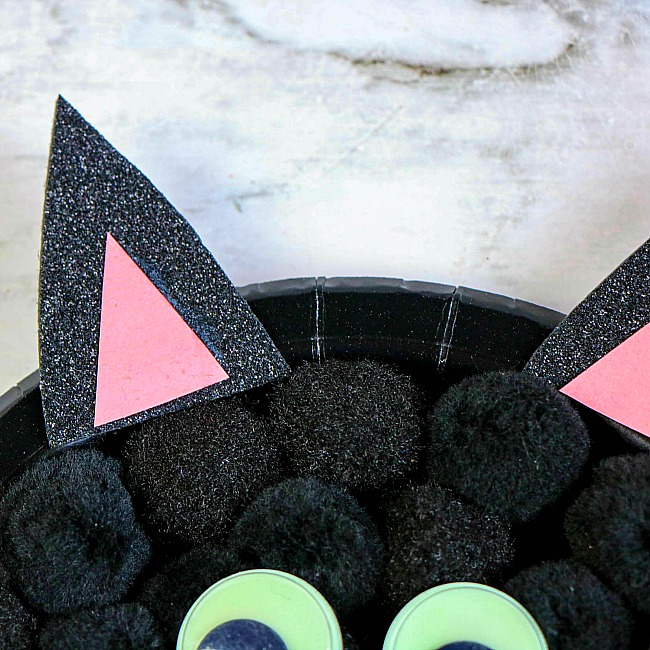 Glue the black triangles to the top edge of the paper plate where the ears would be positioned.